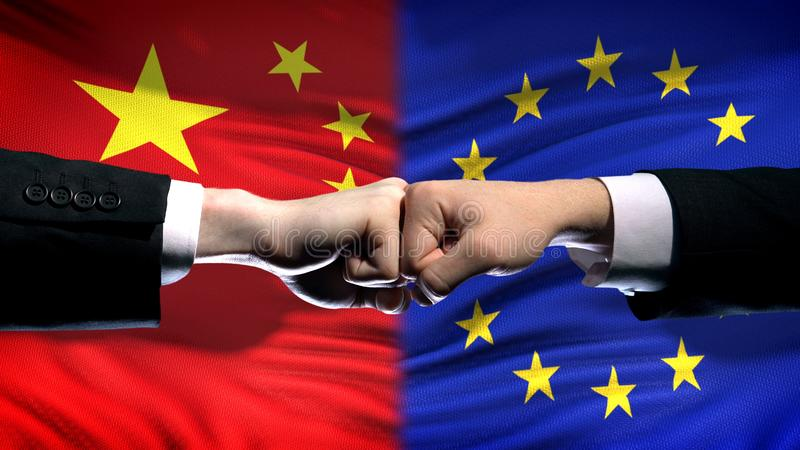 China vs EU conflict, international relations crisis, fists on flag background. Stock photo royalty free stock image