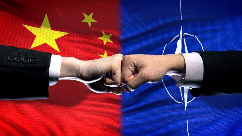 China vs NATO conflict, international relations crisis, fists on flag background stock photography