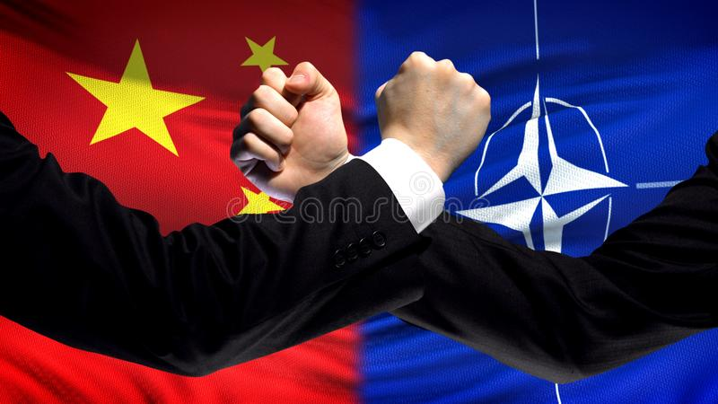 China vs NATO confrontation, countries disagreement, fists on flag background royalty free stock photo
