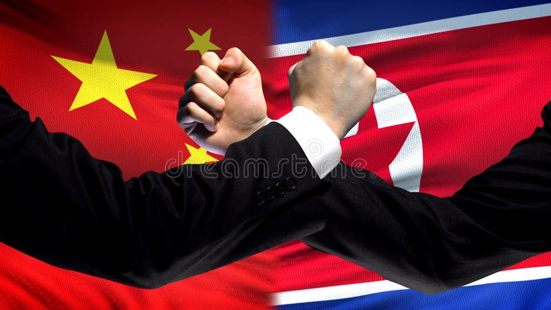 China vs North Korea confrontation fists on flag background, diplomatic conflict royalty free stock photos