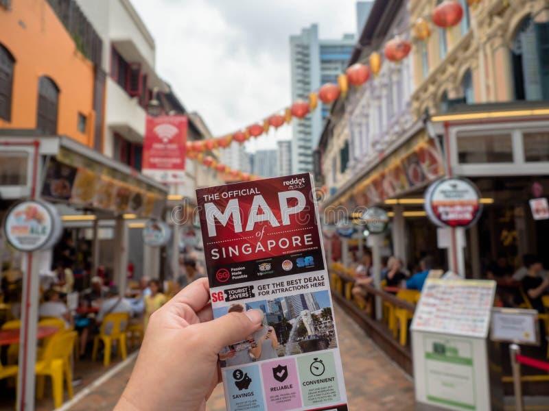 Chinatown SINGAPUR, NOV, - 25, 2018: Mężczyzna trzyma mapę Singapur i tło jest Chinatown Singapur fotografia royalty free