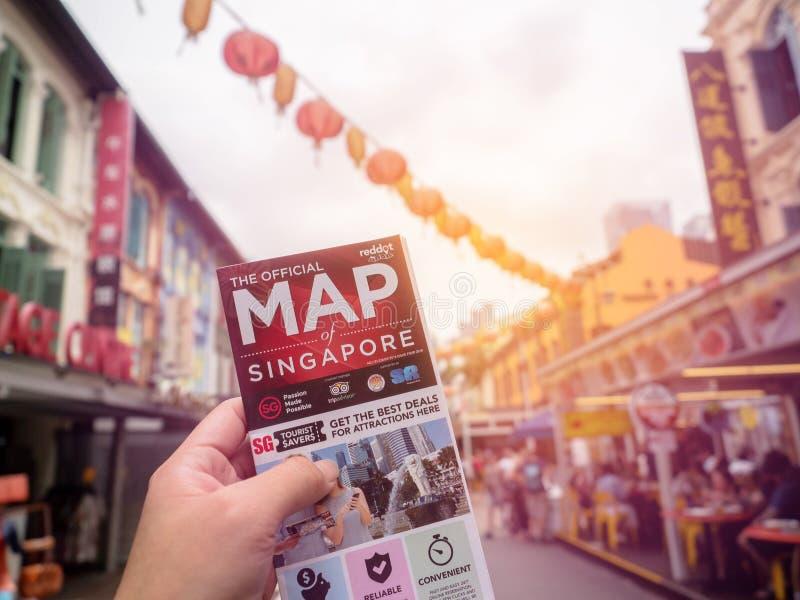 Chinatown SINGAPUR, NOV, - 25, 2018: M??czyzna trzyma map? Singapur i t?o jest Chinatown Singapur obrazy royalty free
