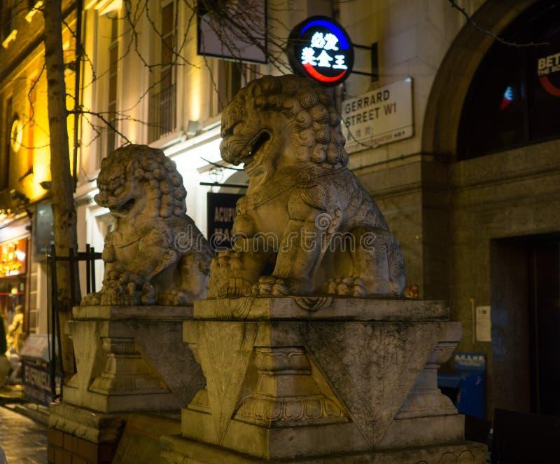 Chinatowndistrict bij nacht in Londen, Engeland met Chinese leeuwstandbeelden op Gerard Street stock foto