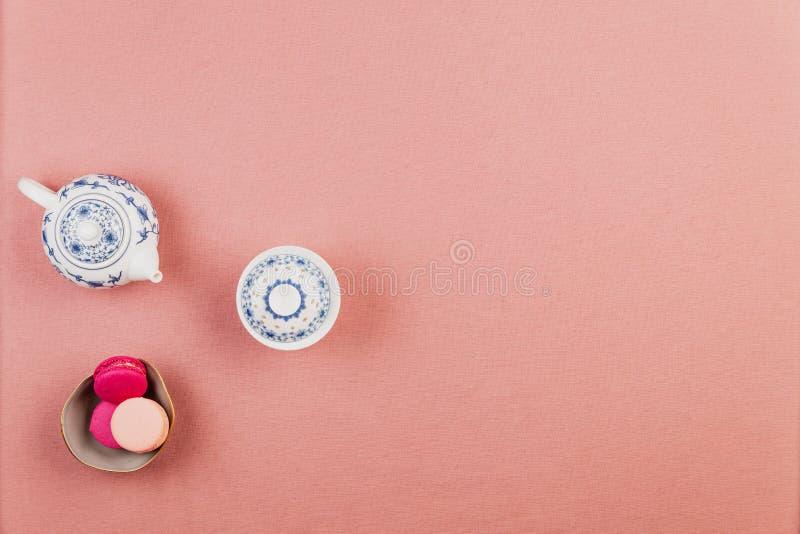 Chinawareteekanne und -schüssel über einem rosa Tischdeckenhintergrund mit rosa französischen macarons oder Makronen, in einer Sc stockfotos