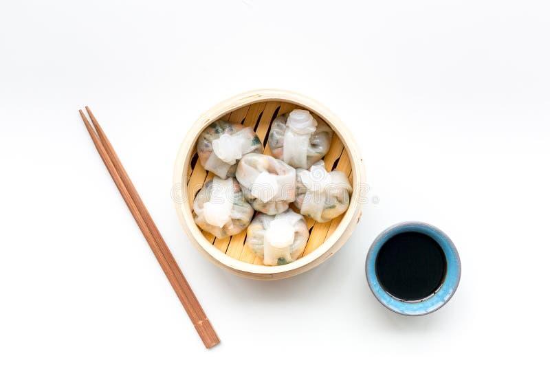 Chinees die voedsel met dim sum, stokken en thee op witte hoogste mening wordt geplaatst als achtergrond stock foto's
