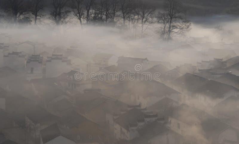 Chinees dorp in ochtendmist stock afbeeldingen