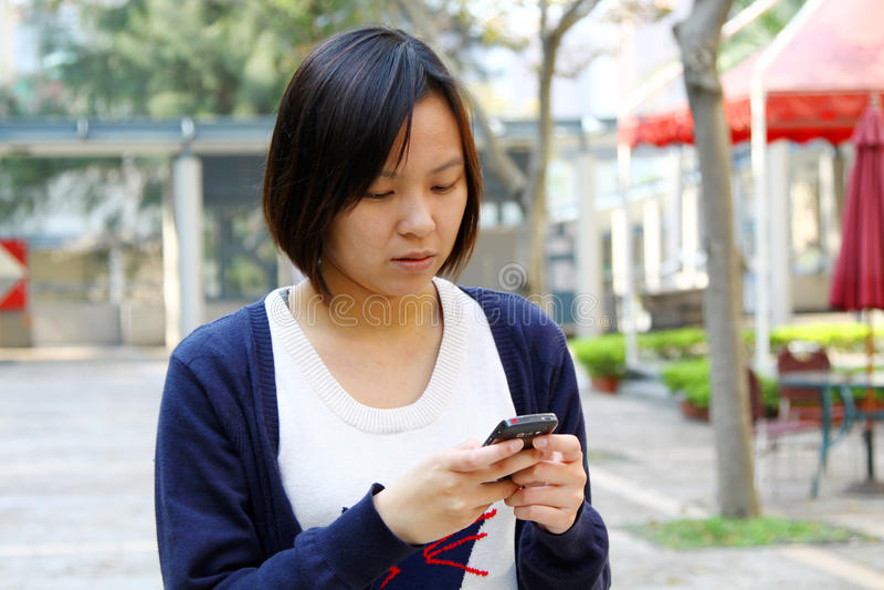 Chinees meisje dat zich op telefoon concentreert stock afbeeldingen