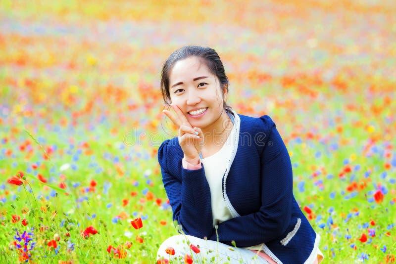 Chinees meisje in het midden van het gebied van multi-colored bloemen stock foto