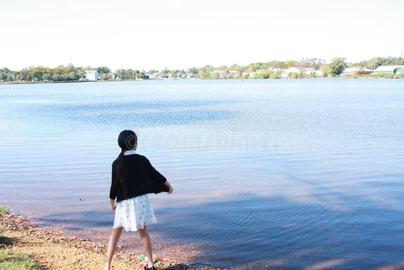 Chinees meisjeskind die steen in het water werpen stock afbeelding
