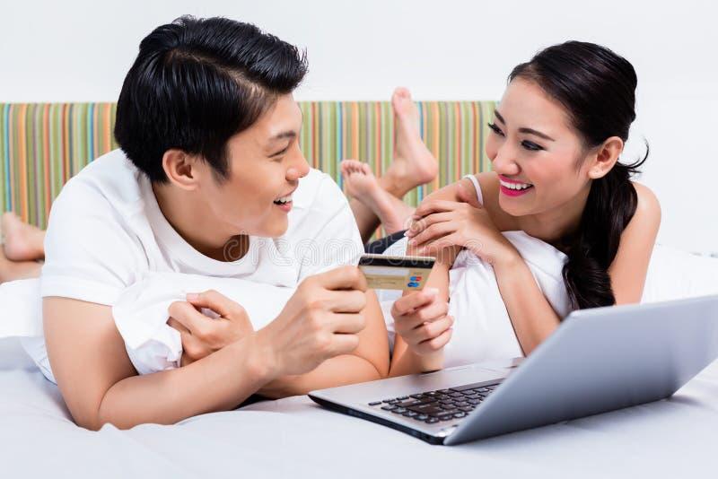 Chinees paar die online van hun slaapkamer winkelen stock foto's