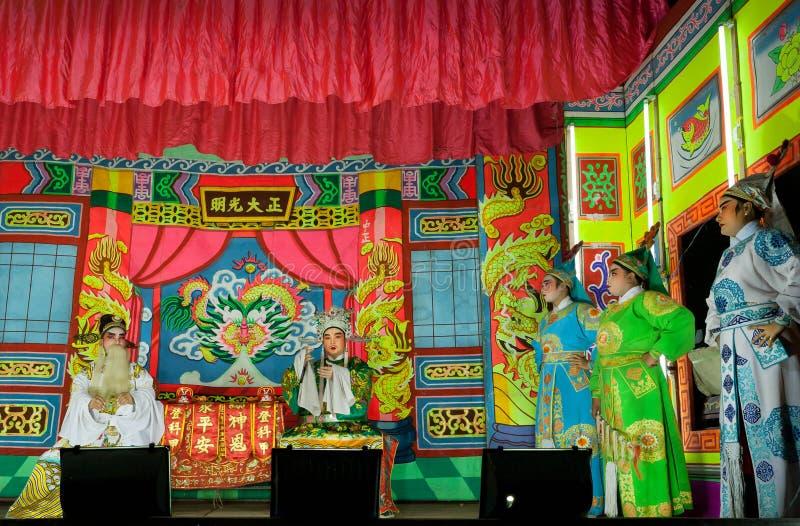 Chinees theaterspel met actoren in tradional costums op colorfullstadium stock afbeelding