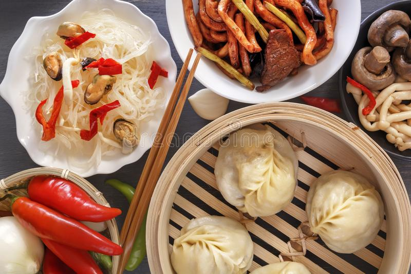 Chinees voedsel op een grijze houten lijst Traditionele stoombollen, noedels, groenten, zeevruchten stock fotografie