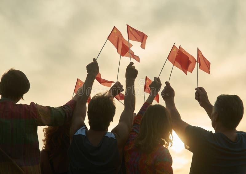 Chineese patrioter med utomhus- flaggor royaltyfria foton
