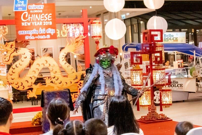 Chinese acteur in het masker die de magische trucs uitvoeren aan de klant die die in Bleport-winkelcomplex het vieren winkelen royalty-vrije stock afbeeldingen