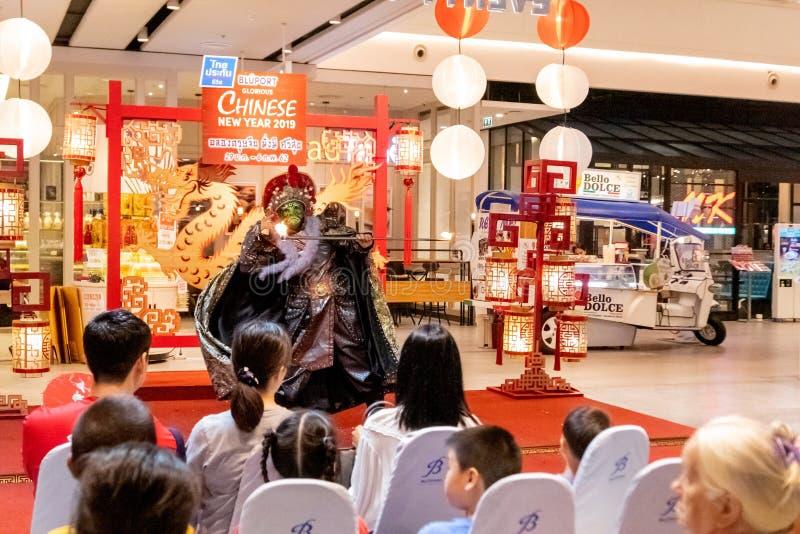 Chinese acteur in het masker die de magische trucs uitvoeren aan de klant die die in Bleport-winkelcomplex het vieren winkelen stock foto's