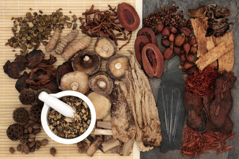 Chinese Alternative Herbal Medicine. Traditional chinese herbal medicine selection with acupuncture needles and mortar and pestle forming a background royalty free stock photography