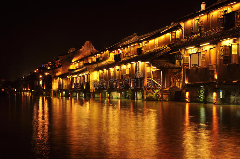 Chinese ancient town at night. The buildings nearby the river are so old but really beautiful stock image