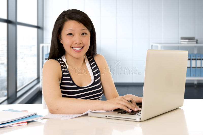 Chinese asian woman working and studying on her laptop at modern office computer desk stock images