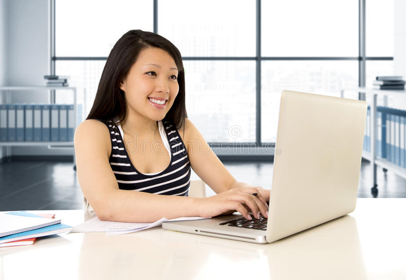 Chinese asian woman working and studying on her laptop at modern office computer desk royalty free stock photos
