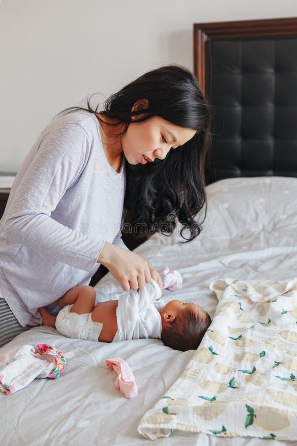 Chinese Aziatische bezige moeder veranderende luier voor pasgeboren zuigelingsbaby stock afbeelding
