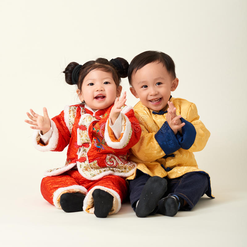 Chinese baby boy and girl in traditional Chinese New Year outfit stock photo