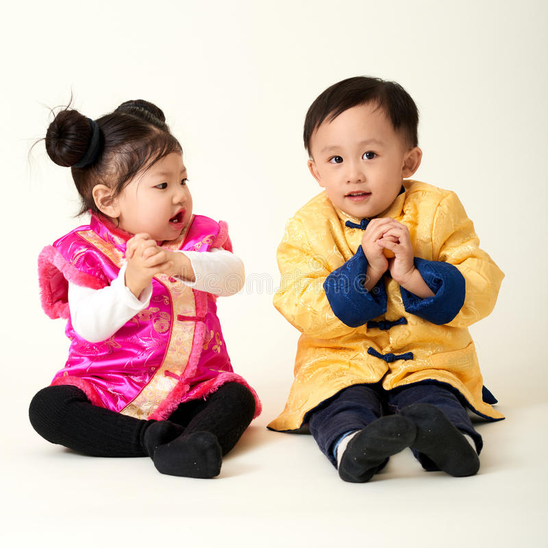 Chinese baby boy and girl in traditional Chinese New Year outfit stock photography