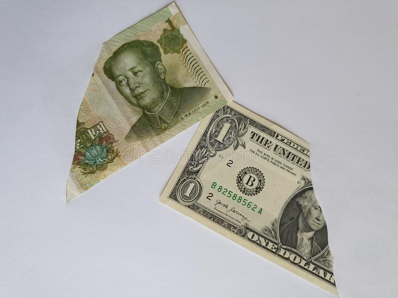 Chinese banknote of one yuan and American one dollar bill on the broken sheet of paper. Commerce, exchange, trade, trading, value, buy, sell, profit, price royalty free stock photography