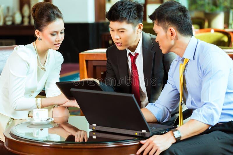 Chinese bedrijfsmensen op vergadering in hotelhal royalty-vrije stock afbeeldingen