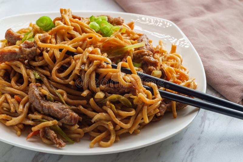 Chinese Beef Lo Mein. Eating Chinese beef lo mein noodles with chopsticks stock images