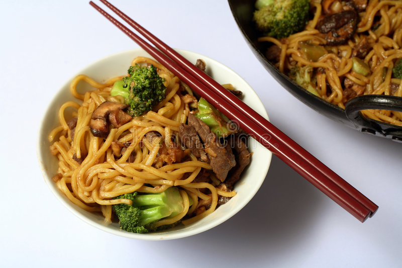 Chinese beef noodle chow mein. Beef chow mein and a chopsticks from above, with part of the wok in the background stock photos