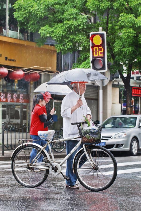 Chinese bejaarden met fiets en paraplu op een regenachtige straat, Shanghai, China stock afbeelding