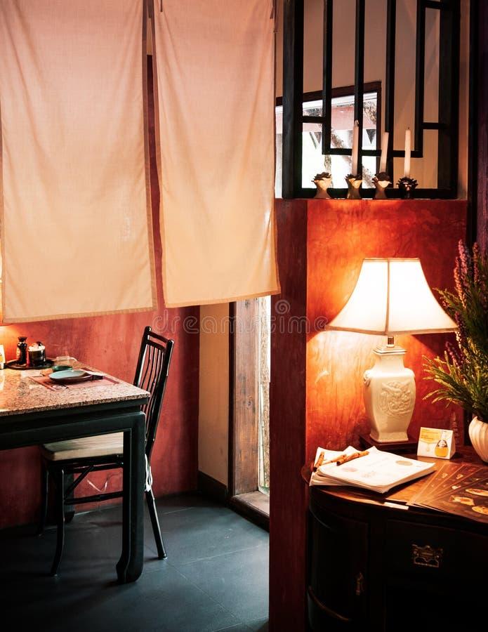 Chinese binnenlandse dinning ruimte met lamp, lijst, houten stoel en royalty-vrije stock afbeelding