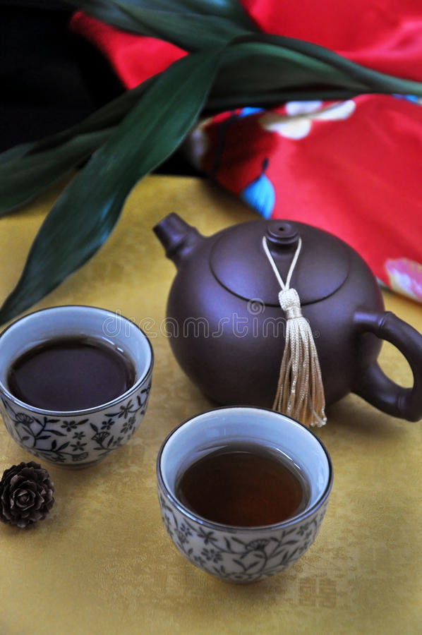 Chinese Black Tea Cup with Pot on Golden Background stock image