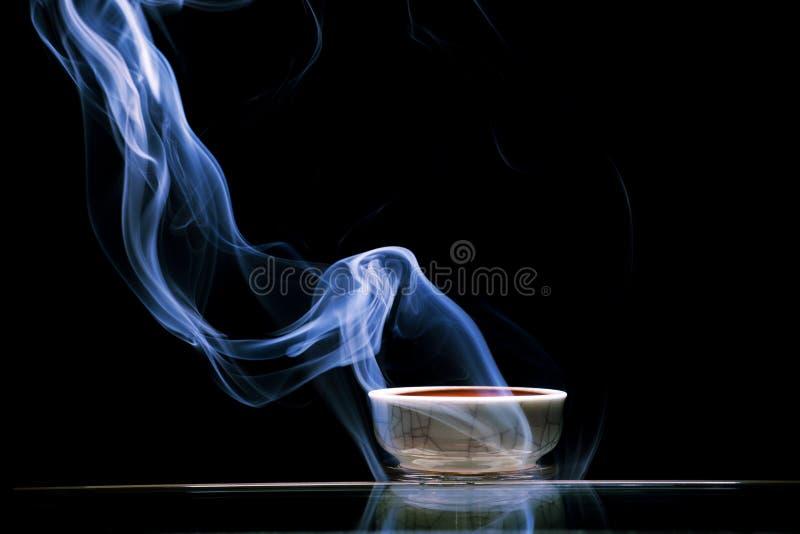 Chinese black tea cup smoke dark background nobody royalty free stock photo