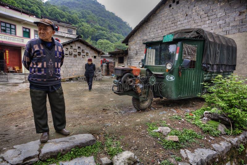 Chinese boeren in dorpsstraat, naast three-wheeled groene auto royalty-vrije stock foto