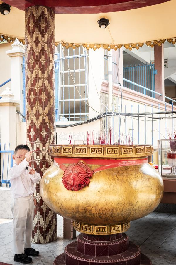 Chinese boy with white dress putting incense stick onto a large joss pot royalty free stock photo