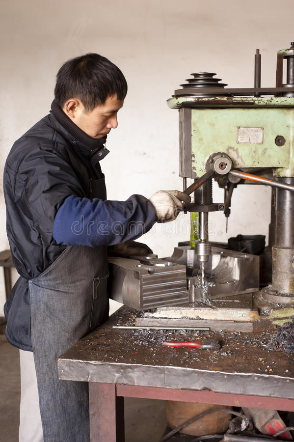 Chinese boy working in a factory royalty free stock image