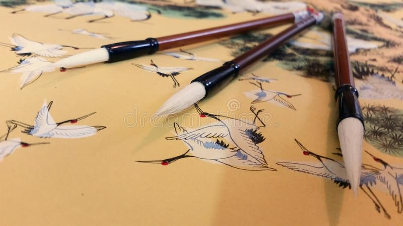 Chinese brushes on traditional style crane painting. Beijing, March 2016 stock photos
