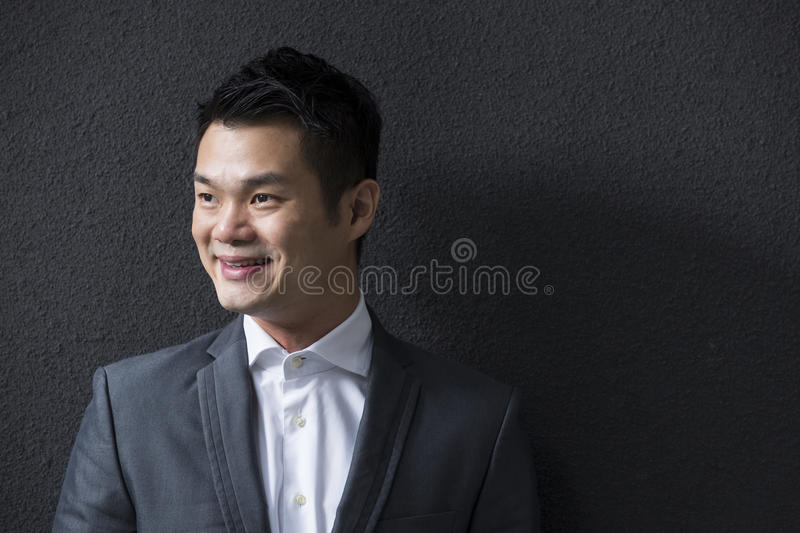 Download Chinese Business Man Leaning On A Black Wall Looking Away. Stock Image - Image: 29530299