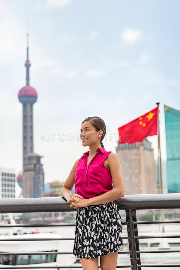 Chinese business woman portrait in Shanghai city by the Bund with the Oriental Pearl tower and China flag in the background. Asian stock photos