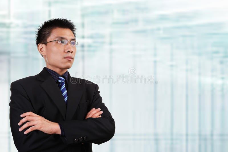 Chinese businessman. In full attire looking away to empty space with blur glass window background stock photos