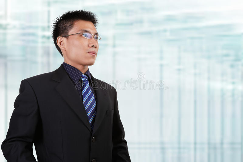 Chinese businessman. In full attire looking away to empty space with blur glass window background stock photography
