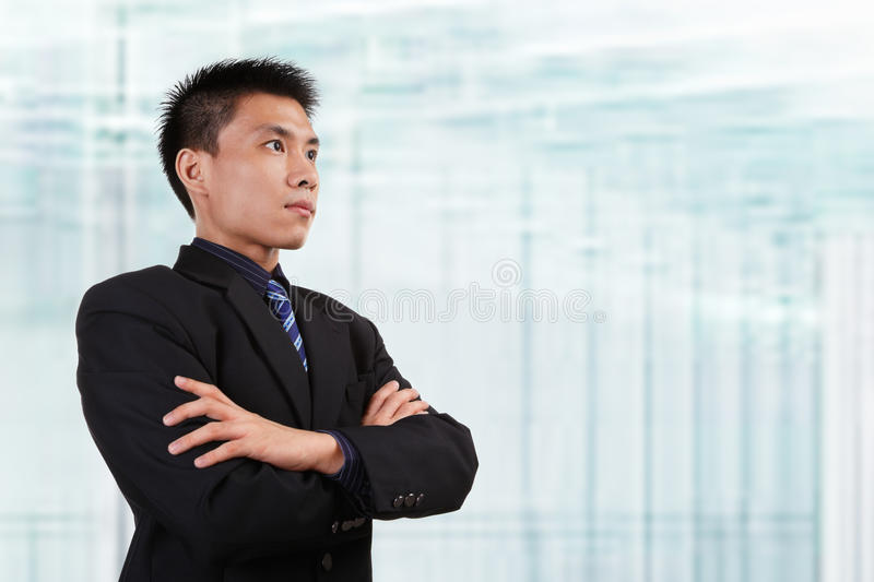 Chinese businessman. In full attire looking away to empty space with blur glass window background stock images