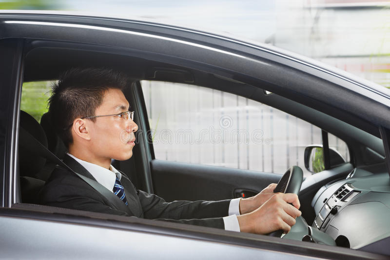 Chinese businessman driving car. Chinese businessman driving a car looking to the front royalty free stock photos