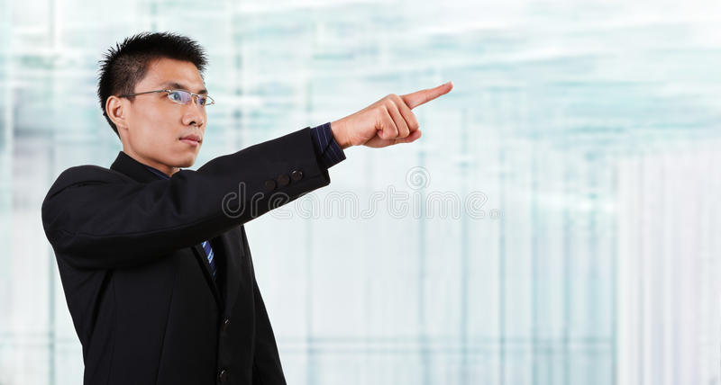 Chinese businessman pointing to empaty space. Chinese businessman in full attire pointing his hand to empty space with blur glass window background royalty free stock images