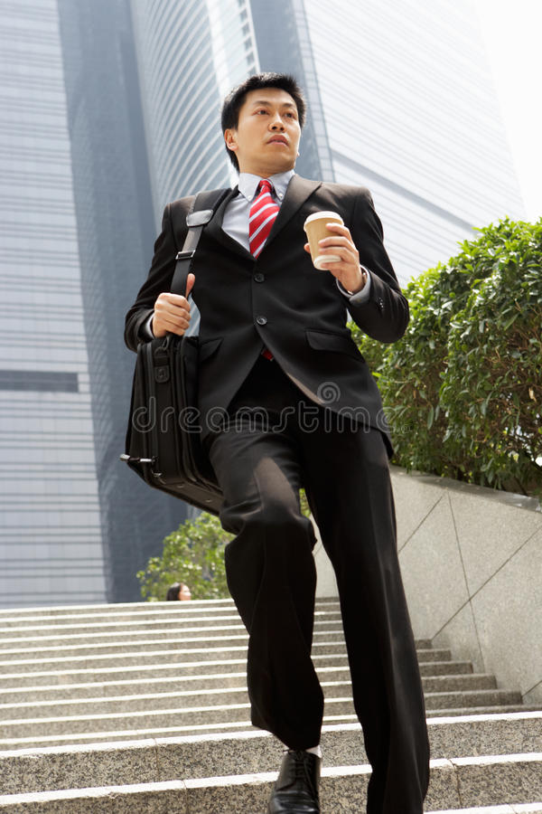 Chinese Businessman Rushing Down Steps Carrying Ba royalty free stock photos