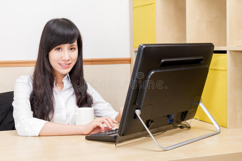 Chinese Businesswoman smiling at desk stock images