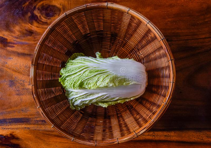 Chinese cabbage in a brown wooden basket placed on the brown wooden floor. close up of isolated chinese cabbage royalty free stock photo