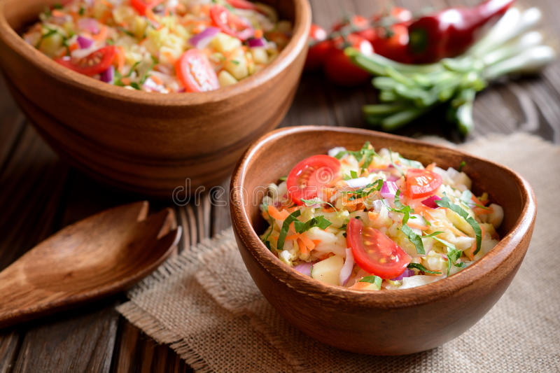 Chinese cabbage salad with carrot, red onion and apples. In a wooden bowl stock photos