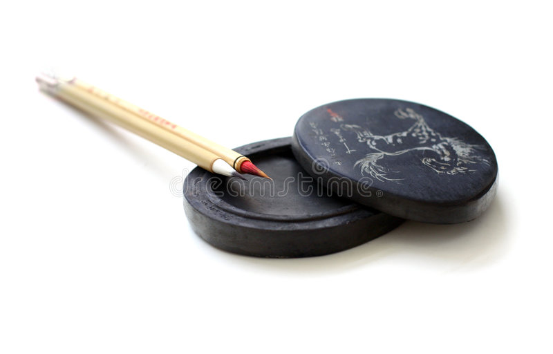 Chinese calligraphy brushes. A pair of slim antique bamboo made chinese calligraphy or paint brushes, arranged neatly on an old ink stone or ink well for stock photography